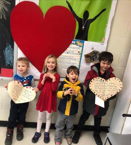 Three children around 5-7 years old stand in a church hallway holding up heart-shaped letters they wrote to the prime minister.