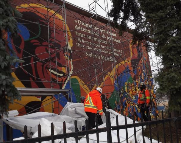 A photo of the large mural of Nelson Mandela on the outside wall of Union United Church in Montreal, just after it was unveiled. It features a large image of Mandela smiling and lifting his arm, along with a quote from him.