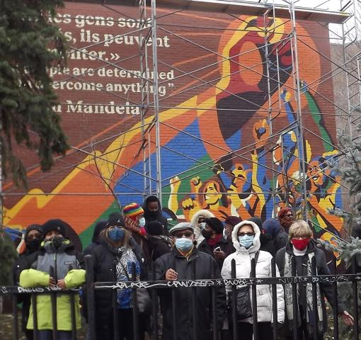 A diverse group of artists and congregation member stand before the huge Mandela mural just after unveiling. They are bundled up against the cold and wearing pandemic masks.