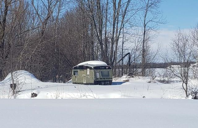 A photo of a trailer home in a snowy landscape.