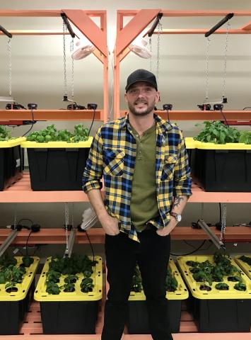 Jesse stands in the ydroponic greenhouse at Stella's Circle.