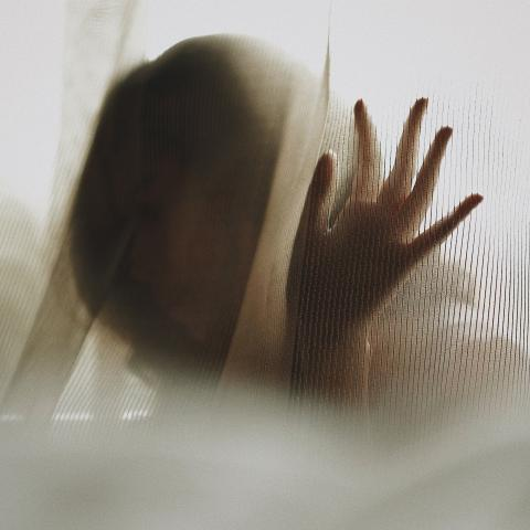 A woman's silhouetted face is mostly blurred by the curtain she's behind.