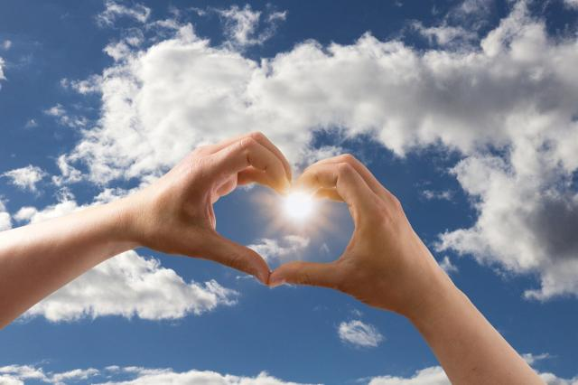 Two hands form a heart against a backdrop of a blue sky with white clouds.
