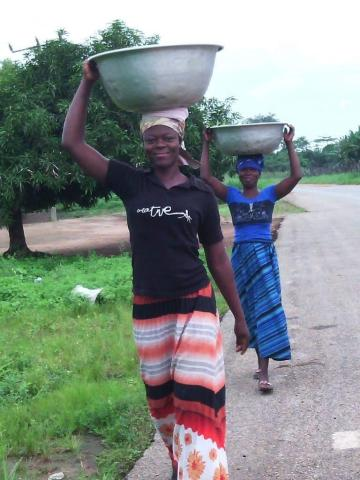 Two Zambian women walk along a road carrying large metal tubs on their heads.