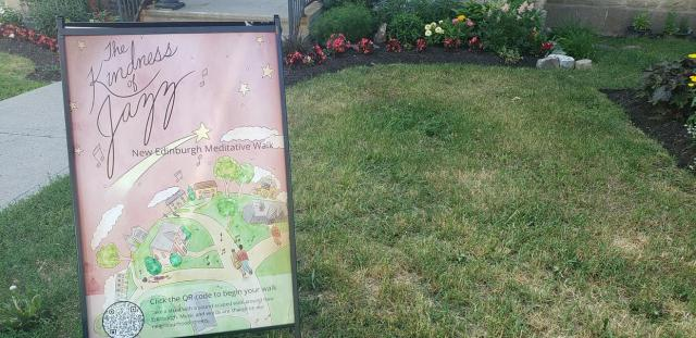 A signboard holding a poster with the words The Kindness of Jazz on a background illustration of people walking paths is displayed on a lawn.