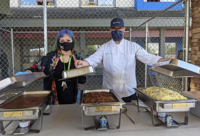 A woman and man wearing masks serve food from behind a table outdoors