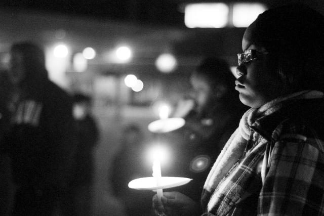 A man stands with a candle during a night time vigil.