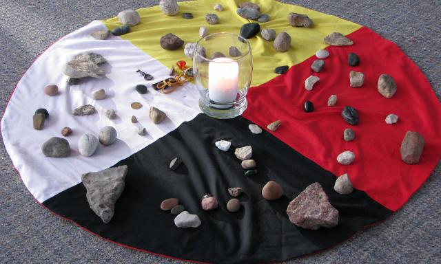 Photo of cloths combined to make an aboriginal medicine wheel with stones placed atop