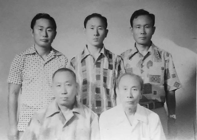 In an aging black and white photo taken sometime around the Korean War, four Korean brothers and their older father face the camera for a formal photo.