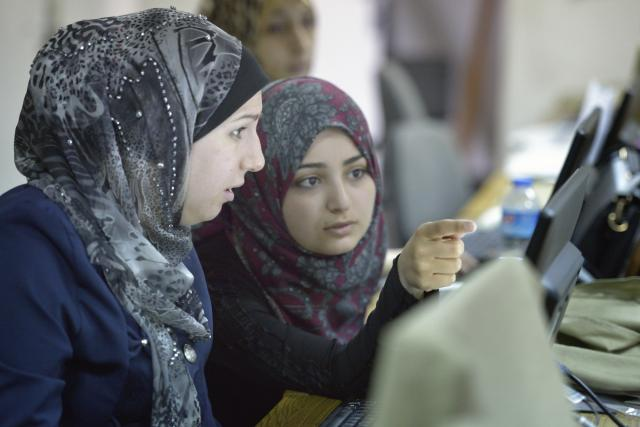 Close-up of women in discussion in front of a computer screen.