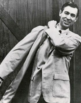 A black and white photograph of Fred Rogers taken in the late 1960s. He is a White man with dark hair and an inviting smile. He is shown wearing a light coloured suit jacket while pulling a bag over his shoulder.