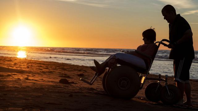 A person in a beach wheelchair crosses the sand while silhouetted by the brillant sunset.