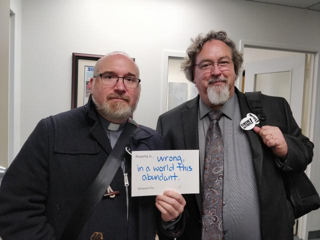 "Moderator Richard Bott holds a sign that says ""poverty is wrong, in a world this abundant"" and stands to the left of a colleague from the Canadian Council of Churches."