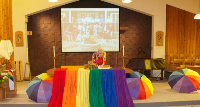 A minister stands in front of a church altar decorated for a Pride celebration with rainbows.