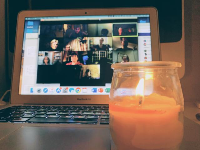 A lit candle is in front of a laptop that displays a Zoom meeting in progress.