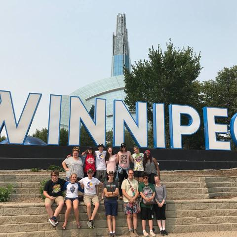 The group of GC43 Pilgrims gather around a huge Winnipeg sign during their visit to the Conference of Manitoba and Northwestern Ontario